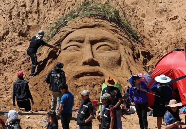 Artistas realizan una escultura de arena con temática de Semana Santa. EFE